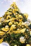 Duża piękna choinka dekorująca z ornament złotymi srebnymi wiszącymi piłkami kłania się girlandy lśnienia światła w europejskim m obraz royalty free