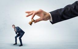 Duża ręka z bierka puszka biznesmena małym słabym pojęciem zdjęcia royalty free