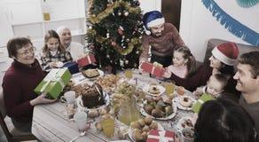 Duża rodzina wymienia prezenty podczas Bożenarodzeniowego gościa restauracji Obraz Stock