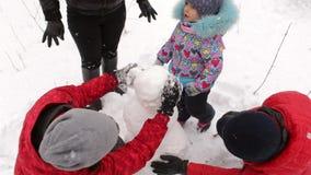 Duża rodzina z dziećmi robi bałwanu w parku zbiory