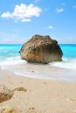 Duża skała na pogodnej plaży z błękitnym niebem i morzem fotografia stock