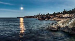 Duża skała przy zmierzchu błękitnym morzem i blask księżyca w odległości fotografia stock