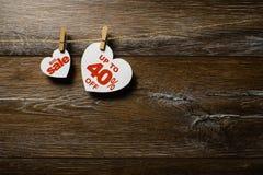 Duża sprzedaż na sercach wiesza na arkanie z clothespins nad drewnianym tłem Czterdzieści procentów dyskontowa promocja pisać na  zdjęcia stock