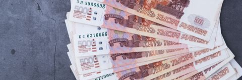 Du?a sterta Rosyjscy pieni?dzy banknoty pi?? tysi?cy rubli k?ama fan na popielatym cementowym tle fotografia stock