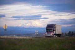 Duża takielunku semi ciężarówka na prostej drodze z śnieżnym góra kapiszonu backgro fotografia royalty free