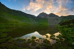 Duża wysokość wysokogórski jezioro w idyllicznej ziemi once zakrywającej lodowami Majestatyczny skalisty halny szczyt jarzy się p Zdjęcia Stock