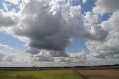 Duże cumulus chmury nad pola Zuidplaspolder w holandiach i łąki obrazy royalty free
