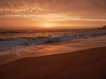 Duże fale łamają na plaży przy zmierzchem w Portugalia z pięknym niebem fotografia stock