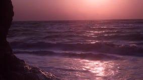 Duże fale, piana, przepływ, na glinianej górze, przeciw tłu pomarańcze świt zdjęcie wideo