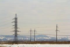 Dużej mocy powerline słupy z wysokim woltażem depeszują przez pola Zdjęcia Stock