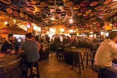 Dużo pije ludzi wśrodku starego prętowego delirium z retro meble i drewnianymi piwnymi baryłkami Obrazy Royalty Free