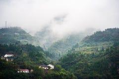 Dużo stwarzają ognisko domowe w dolinnym pobliskim jangcy w deszczowym dniu, mgiełka pławik nad górą obrazy royalty free