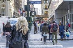 Dużo zaludniają odprowadzenie na E 42nd St z budynkiem w tle w Miasto Nowy Jork, NY zdjęcie royalty free