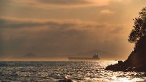 Duży ładunku statek blisko do brzeg w podeszczowej chmurze w zmierzchu Zdjęcia Royalty Free