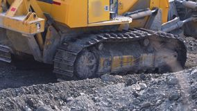 Duży żółty ekskawator pracuje blisko fabrycznego zakończenia w górę zdjęcie wideo