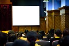 Duży biały pusty ekran w dużym pokoju konferencyjnym z zamazywał wiele ludzi zdjęcie stock
