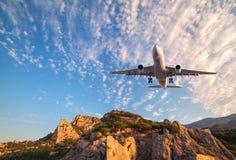 Duży biały samolot lata nad skałami przy wschodem słońca Obrazy Stock