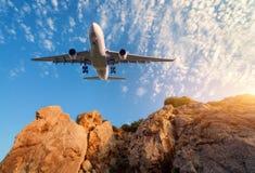 Duży biały samolot lata nad skałami przy zmierzchem Obraz Royalty Free