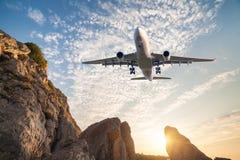 Duży biały samolot lata nad skałami przy zmierzchem Zdjęcia Stock