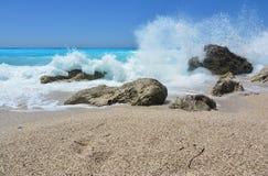 Duży, bryzgający macha obejmowanie skały w płytkim morzu obraz royalty free