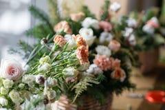 Duży bukiet świezi kwiaty, brzoskwinia goździk i białe róże w łozinowym koszu na drewnianym stole, domowy wystrój, rocznik Zdjęcia Stock