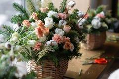 Duży bukiet świezi kwiaty, brzoskwinia goździk i białe róże w łozinowym koszu na drewnianym stole, domowy wystrój, rocznik Zdjęcia Royalty Free
