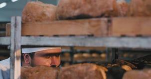 Duży główny piekarz w piekarni kuchni cieszy się odór świeży piec chleb od półek, robi ślicznej twarzy zbiory