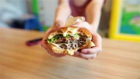 Duży hamburger w rękach kobieta zamazujący tło zbiory