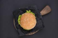 Duży hamburger z sezamowymi ziarnami na czarnym tle Fast food i bezpłatna przestrzeń dla teksta na widok obrazy stock
