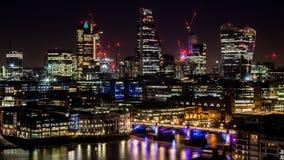 Duży miasto góruje przy nocą z światłami i odbiciami w rzece obrazy stock