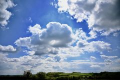 Du?y niebo - Pogodne chmury Nad Wiejskim po?o?eniem obrazy royalty free