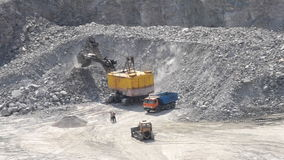 Duży ogromny żółty ekskawatoru wiadro łyżkuje up wielkiego kamienia granit i nalewa zakończenie, zdjęcie wideo