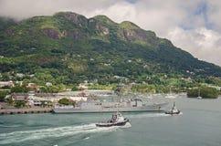 Duży okręt wojenny z swój personelem na pokładzie i dwa pociągamy łodzie w porcie Fotografia Royalty Free