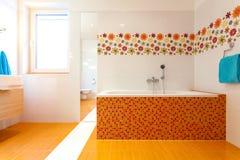 Duży pomarańcze skąpanie w ślicznej współczesnej łazience fotografia stock