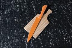 Duży pomarańczowy kuchenny nóż na drewnianej tnącej desce na czerń stole Zdjęcia Stock