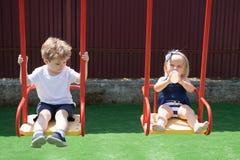 Duży przygody boisko Dziewczyny i chłopiec ostrzyżenia style Mali dzieci z blondynem na huśtawce Mały brat i obraz royalty free