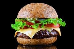 Duży smakowity cheeseburger na czarnym tle z piec na grillu mięsem lub hamburger, ser, pomidor, bekon, cebula Hamburgeru zbliżeni obrazy royalty free