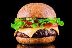 Duży smakowity cheeseburger na czarnym tle z piec na grillu mięsem lub hamburger, ser, pomidor, bekon, cebula Hamburgeru zbliżeni zdjęcia stock