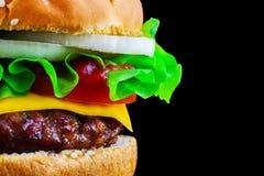 Duży smakowity cheeseburger na czarnym tle z piec na grillu mięsem lub hamburger, ser, pomidor, bekon, cebula Hamburgeru zbliżeni obrazy stock