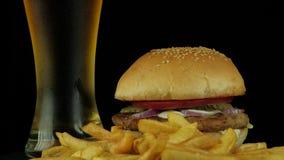 Duży smakowity hamburger z kurczakiem, piwem i dłoniakami kartoflanymi, zdjęcie wideo