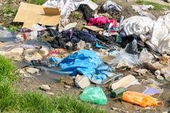 Duży stos śmieci i dżonka w wodzie rzecznej zanieczyszcza naturę z ściółką zdjęcia stock