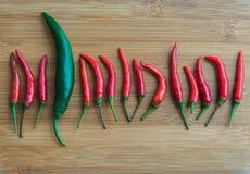 Duży zielony chili pieprz w małym Czerwony chili pieprzu na ciapanie bloku Zdjęcia Royalty Free
