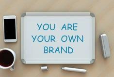 Du är ditt eget märke, meddelandet på whiteboard, den smarta telefonen och kaffe på tabellen arkivbilder