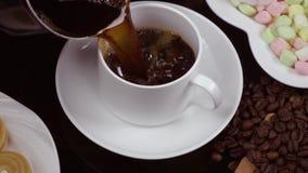 Du café noir chaud est versé dans une tasse blanche Mouvement lent clips vidéos