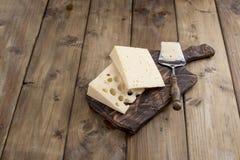 Du fromage avec des trous est coupé en parties sur un panneau en bois, des laitages utiles Nourriture savoureuse Photo de style c photo stock