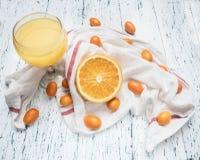 Du jus sain de matin de nourritures des oranges et du kumquat, fruits sont présentés sur une serviette blanche, verre rempli du j images stock