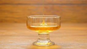 Du miel est versé dans un bol en verre (le NO1) banque de vidéos