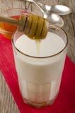 Du miel est versé dans un verre de lait chaud Photographie stock