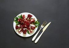 Du plat blanc un fruit, une fourchette et un couteau cassés mûrs de grenade d'isolement sur un fond noir Image stock