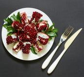 Du plat blanc un fruit, une fourchette et un couteau cassés mûrs de grenade sur un fond noir Images libres de droits